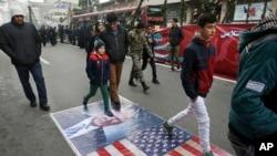 Des Iraniens marchent sur le portrait de Donald Trump et le drapeau des Etats-Unis, le 10 février a Teheran.