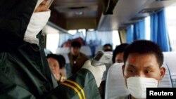 一名中國醫務人員在高速公路上的檢查站為一名長途客車上的旅客量體溫。(2003年5月10日)
