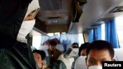 Seorang pekerja medis China memeriksa suhu seorang pendatang di sebuah pos pemeriksaan di jalan bebas hambatan menuju Wuhan, ibu kota provinsi Hubei, 10 Mei 2003. (Foto: Reuters)
