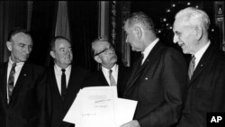 U.S. President Lyndon B. Johnson holds the signed document of the Voting Rights Act of 1965 Aug. 6, 1965.