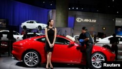 A man cleans a Jaguar at the 2013 Los Angeles Auto Show.