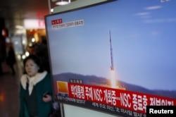 2016年2月7日,韩国首尔火车站,一位旅客走过正在显示北朝鲜发射远程火箭新闻的电视屏幕。
