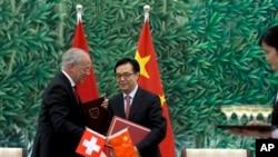 Menteri Perdagangan China, Gao Hucheng, dan Menteri Ekonomi Swiss, Johann Schneider-Ammann menandatangani kesepakatan perdagangan bebas di Beijing, Sabtu (6/7).