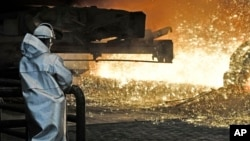 FILE - In this April 27, 2018 photo a steel worker watches the hot metal at the Thyssenkrupp steel factory in Duisburg, Germany.