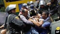 La policía peruana forcejea con un manifestante, durante la reubicación de los vendedores del mercado La Parada, en Lima, el sábado 27 de octubre de 2012.