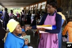 A MSF worker takes details from patients at a clinic in southern Zimbabwe