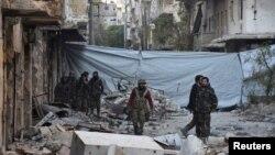 지난달 28일 시리아 정부군이 알레포 인근 알-사크아우르 지역을 점령한 후, 건물 잔해를 수색하고 있다. 저격수의 공격을 막기 위해 천으로 거리를 가렸다.