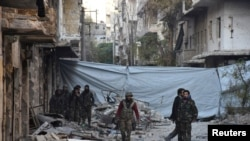FILE - Syrian government soldiers walk amid rubble of damaged buildings after they took control of al-Sakhour neighborhood in Aleppo, in this handout picture provided by SANA, Nov. 28, 2016.