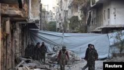 شام کے فوجی حلب کے ایک مضافاتی علاقے پر قبضے کے بعد ایک تباہ شدہ عمارت کے پاس سے گذر ہے ہیں۔ 30 نومبر 2016