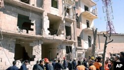 A handout picture released by the official Syrian Arab News Agency (SANA) shows rescue teams inspecting the blast scene in Aleppo March 18, 2012.