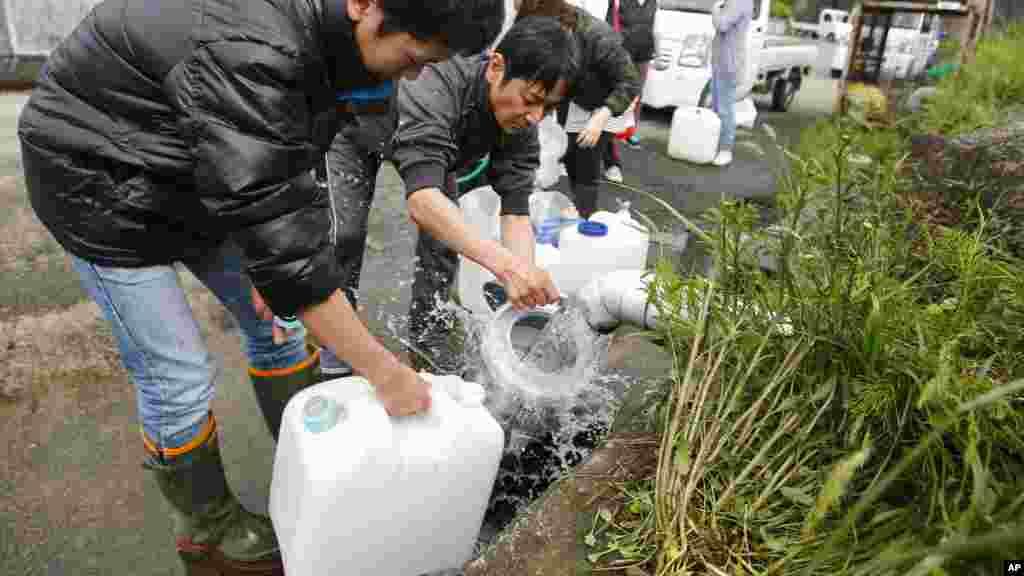 Des habitants récupèrent de l'eau de source dans des bouteilles en plastique à Aso, préfecture de Kumamoto, Japon, 17 avril 2016.