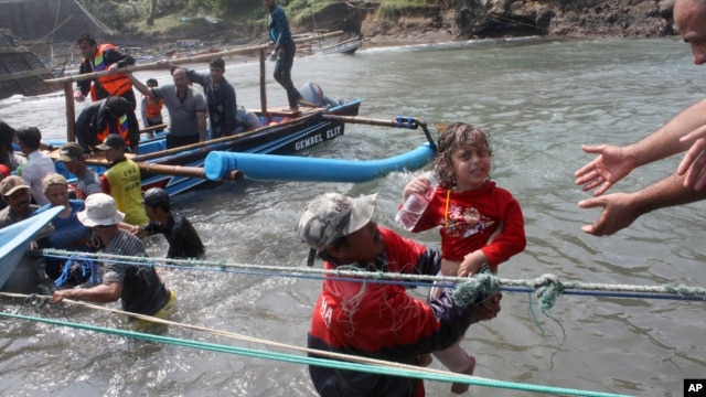 A rescuer carries a child after a boat carrying asylum seekers sank off Java island, in Cianjur, West Java, Indonesia, July 24, 2013.