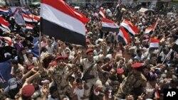 也门反政府示威者6月5日挥舞旗帜,呼喊口号,举起士兵,庆祝总统萨利赫前往沙特阿拉伯接受医疗