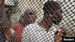 FILE - Prisoners line up inside Douala central prison in Cameroon.