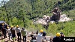 24일 북한 풍계리 핵실험장 폭파 현장을 외국 기자들이 취재하고 있다. 관영 조선중앙통신 배포 사진.