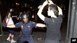 Policemen scuffle with protesters during a demonstration against what they claim is the expensive cost of the papal visit in central Madrid coinciding with the second day of the World Youth Day meeting, August 18, 2011