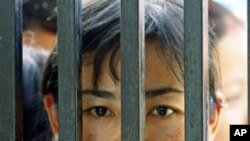 Family members of prisoners wait for their release in front of the Insein Prison gate in Rangoon, Burma, May 17, 2011.