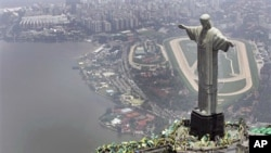 A 2007 file photo of people waving flags at the Christ the redeemer statue in Rio de Janeiro after Brazil was officially chosen by FIFA as host of the 2014 World Cup