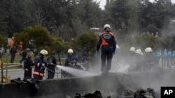 Regu pemadam kebakaran berupaya memadamkan kebakaran akibat jatuhnya helikopter yang membawa tujuh penumpang di jalanan distrik Buyukcekmece, Istanbul, Turki, 10 Maret 2017 (IHA via AP).