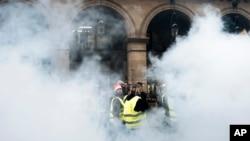 Para demonstran mengenakan rompi kuning berjalan melewati bom asap dekat taman-taman Tuileries di Paris, Sabtu, 22 Desember 2018. (Foto: AP/Kamil Zihnioglu)