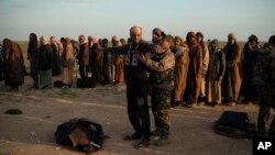 Seorang anggota Pasukan Demokratik Suriah atau SDF memeriksa anggota kelompok militan ISIS yang menyerah di kota Baghuz, Suriah Timur.