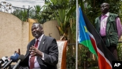 FILE - South Sudan's rebel leader Riek Machar, left, speaks to the media about the situation in South Sudan.