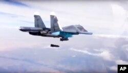 9 ທັນວາ, 2015 ຮູບທີ່ຄັດອອກມາຈາກວີດີໂອ ໂດຍກະຊວງປ້ອງກັນປະເທດຣັດເຊຍ, Su-34 ທີ່ກຳລັງຖິ້ມລະເບີດໃສ່ເປົ້າໝາຍ.