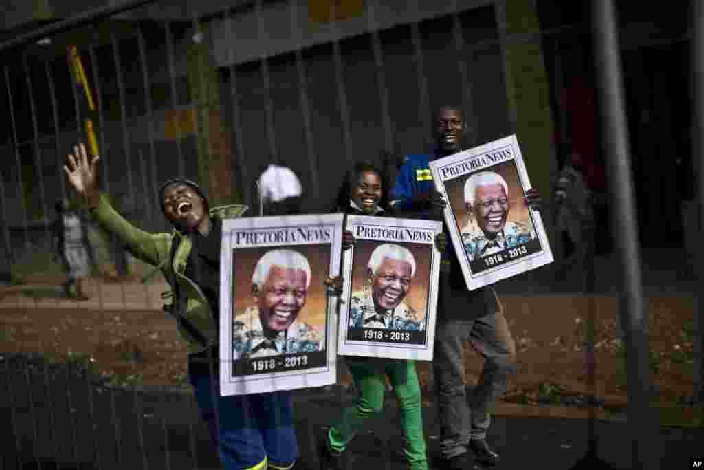 Sul-africanos exibem poster do ex Presidente Nelson Mandela e cantam durante o cortejo fúnebre em Pretoria. Dez. 11, 2013.