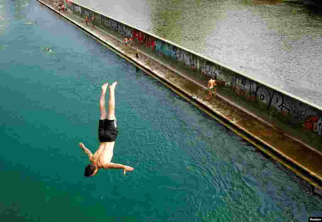 Seorang pria melompat dari sebuah jembatan ke sungai Limmat pada hari yang panas di kota Zurich, Swiss.
