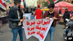 """Người biểu tình giăng biểu ngữ viết """"Iran, Mỹ hãy ra khỏi Iraq. Baghdad tự do"""" trong một buổi tọa kháng tại quảng trường Tahrir ở Baghdad, Iraq hôm thứ Tư 8/1/2020. (AP Photo/Qassim Abdul-Zahra)"""