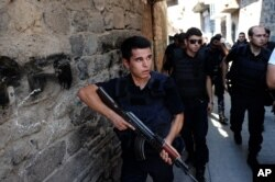 FILE - Turkish police officers conduct a security operation in Diyarbakir, southeastern Turkey, Aug. 15, 2015.