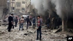This photo released Dec 13, 2015, by the Douma Revolution News Network shows Syrians trying to extinguish a fire that was allegedly caused by Syrian government aerial bombardment on the Damascus suburb of Douma, Syria.