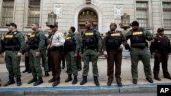 Agentes de la Oficina del Alguacil en Baltimore resguardan la entrada principal de la Corte de Circuito de la ciudad mientras manifestantes protestaban la nulidad del juicio contra el primero de seis policías acusados en conexión con la muerte del detenido estadounidense Freddie Gray.