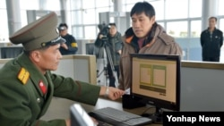 개성공단 전자출입체계(RFID) 시스템이 28일 본격적인 시범 가동에 들어간 가운데 북측 출입사무소의 직원이 전자시스템을 이용해 개성공단 출입 심사를 하고 있다.