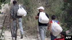 Sirijske izbeglice nose, preko granice sa Turskom, hranu Sirijcima koji još nisu uspeli da pobegnu iz zemlje