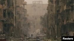 ເດັກນ້ອຍຄົນນຶ່ງ ຍ່າງກາຍຕຶກອາຄານ ທີ່ໄດ້ຮັບຄວາມເສຍຫາຍ ຢູ່ເມືອງ Deir al-Zor (4 ເມສາ 2013)