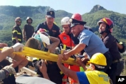 FILE - Firefighters and rescuers pull out a boy, Mattias, from the collapsed building in Casamicciola, on the island of Ischia, near Naples, Italy, a day after a 4.0-magnitude quake hit the Italian resort island, Aug. 22, 2017.
