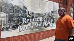 Freeman Culver berdiri di depan mural yang berisi daftar nama-nama usaha yang hancur saat pembantaian rasial warga kulit hitam di Kota Tulsa pada 1921, di Tulsa, Oklahoma, 15 Juni 2020. (Foto: AP)