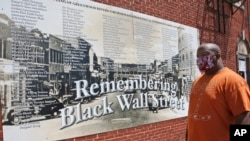 Freeman Culver stands in front of a mural listing the names of businesses destroyed during the Tulsa race massacre in Tulsa, Okla., Monday, June 15, 2020. (AP Photo/Sue Ogrocki)