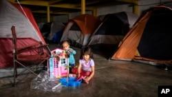 Dos niños de Honduras que esperan con sus familiares para solicitar asilo en EE.UU., juegan en el refugio en el centro de Tijuana, México, el martes 25 de diciembre de 2018.