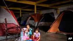 Los niños hondureños juegan con juguetes nuevos en un almacén vacío utilizado como refugio que abrió sus puertas a los migrantes en el centro de Tijuana, México. Foto de archivo.
