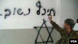 """Seorang tentara Israel menggambar tanda Bintang Daud dan tulisan: """"Akan Kembali Segera"""" di rumah warga Palestina (foto dokumentasi)."""