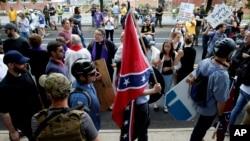 維吉尼亞夏洛特維爾市一名白人至上主義者手持南方邦聯旗從反示威人群中走過。 (2017年8月12日)