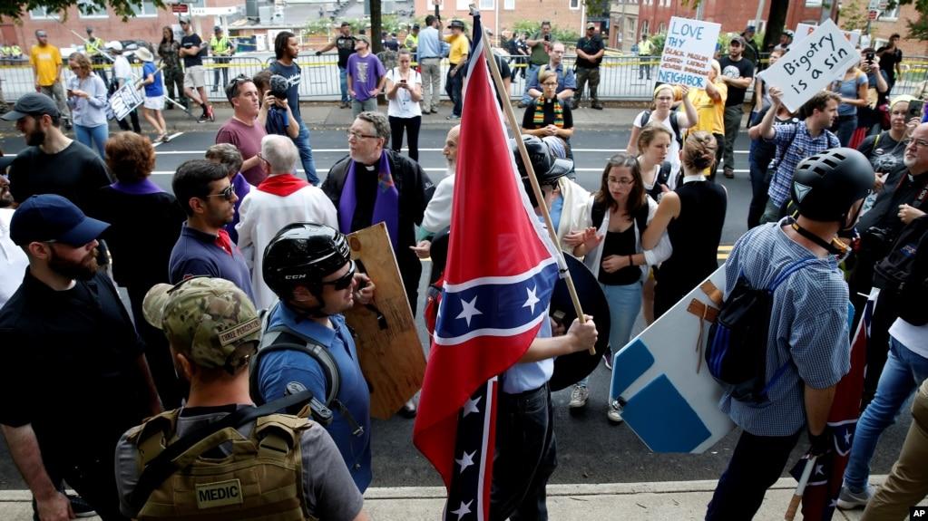 在美国维吉尼亚州夏洛特维尔市的白人至上主义者集会时,一名白人至上主义者打着美国内战中南方邦联的旗帜,走过同他们针锋相对的示威者(2017年8月12日)