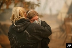 Krystin Harvey, left, comforts her daughter Araya Cipollini at the remains of their home burned in the Camp Fire, Nov. 10, 2018, in Paradise, Calif.