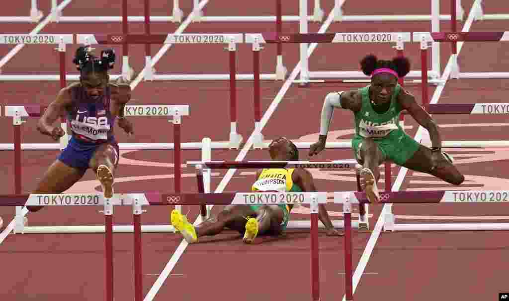 Yanique Thompson, of Jamaica, center, reacts as she pulls up during a women's 100-meter hurdles semifinal at the 2020 Summer Olympics, Sunday, Aug. 1, 2021, in Tokyo, Japan. At left is Christina Clemons, of United States, and at right, Tobi Amusan, of Nigeria. (AP Photo/Charlie Riedel)