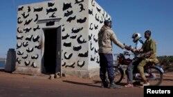 Một binh sĩ Mali kiểm tra căn cước của những người đi qua một cây cầu chiến lược