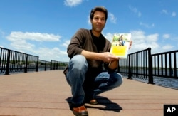 "FILE - David Goldman poses with his book ""A Father's Love"" in Red Bank, N.J., May 5, 2011. Goldman became the poster dad for the issue of international child abductions when his ex-wife ran off with his son, Sean, to Brazil. He finally got custody of his son in 2009."