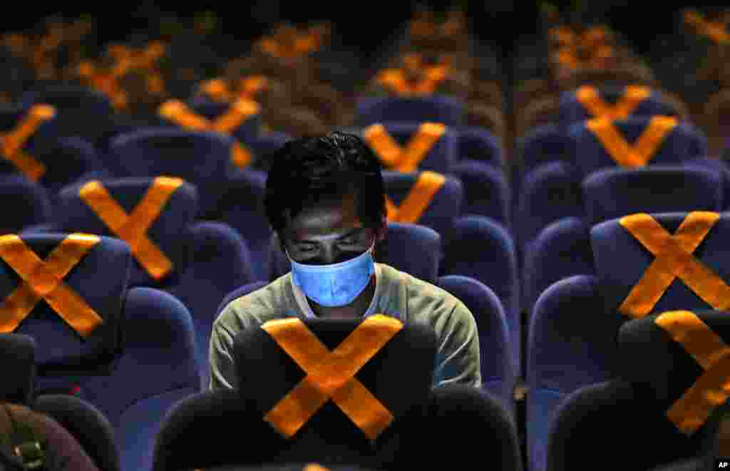 A man checks his mobile phone as he sits amid physical distancing markers prior to the start of a movie at CGV Cinemas theater in Jakarta, Indonesia.