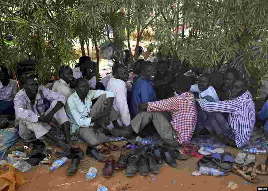 Internally displaced men sit inside a United Nations Missions in Sudan (UNMIS) compound, Juba, South Sudan, Dec. 19, 2013.